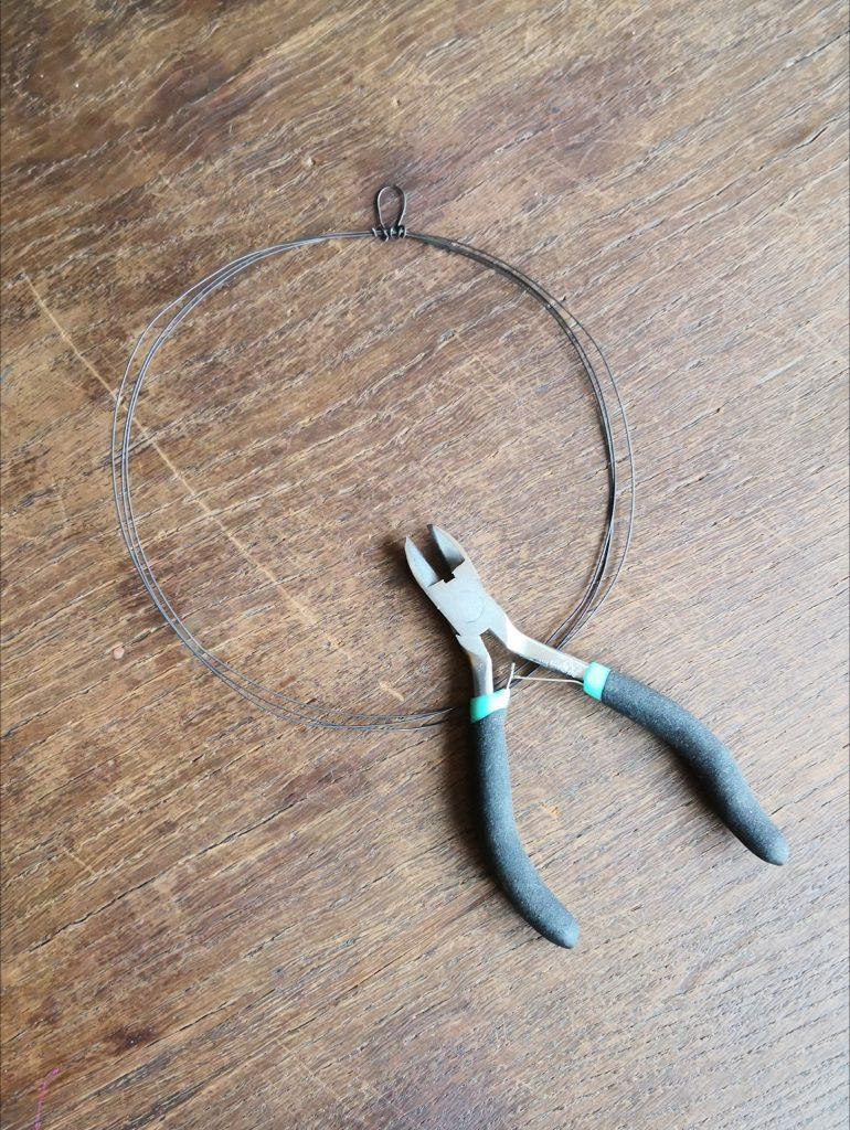 Den Kranz von der Glasschale schieben. Die Enden verdrillen und dabei eine Schlaufe für die Aufhängung biegen. Mit der Flachzange festdrücken.