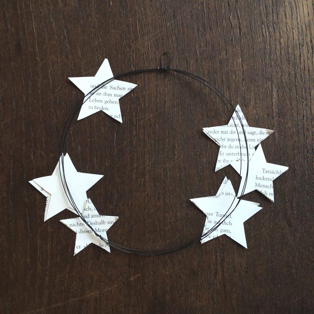 Die flachen Sterne paarweise so auf dem Kranz verteilen, wie du es schön findest.