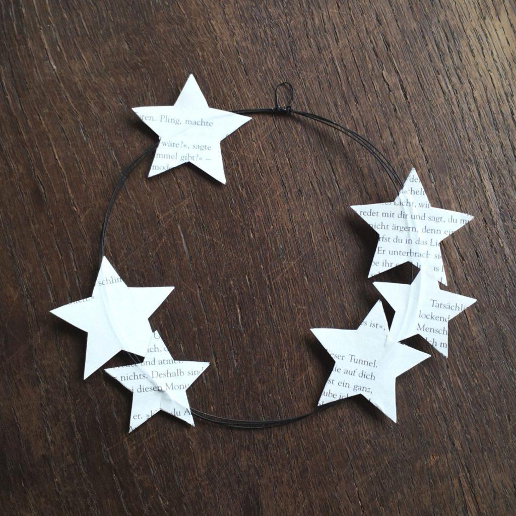 Die Sterne so aufkleben, dass sich der Draht jeweils zwischen zwei Sternen befindet.